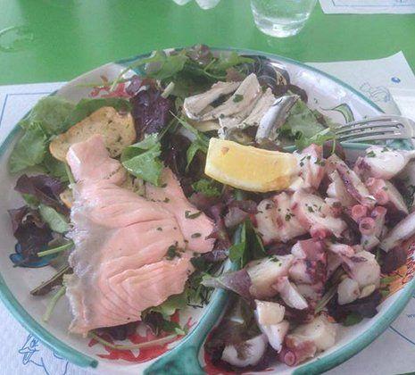 un piatto di polipo e salmone e una fetta di limone