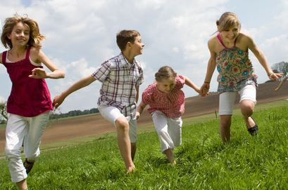 A group of children running hand-in-hand  up a grassy hill