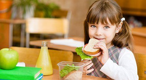A little girl eating a sandwich from a lunch box