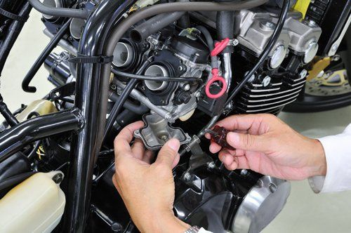mani di operaio mentre lavora su un motore di motocicletta