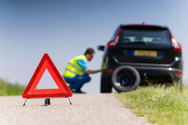 vista di un triangolo su un lato della strada e dietro un uomo con una pettorina giallo fosforescente intento nel sostituire la ruota