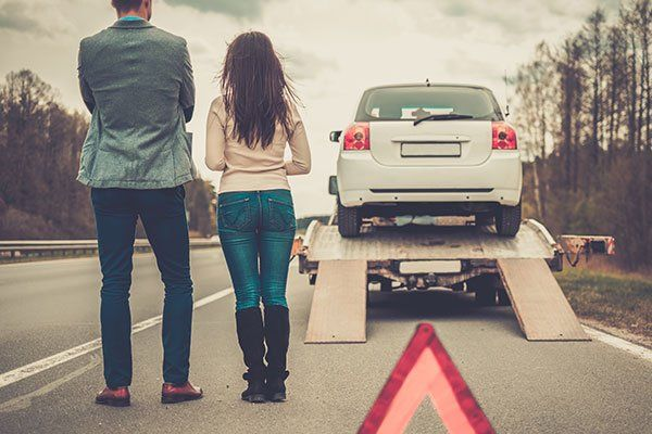Una coppia dietro un'auto caricata su un carro attrezzi