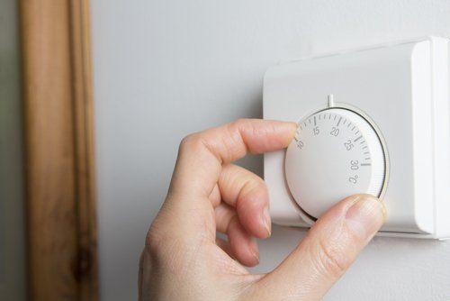 mano che regola un termostato