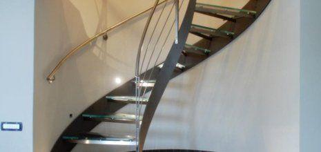 Moderna scala interna in forma di spirale fatta in metallo e la cui ringhiera cromatura questa installata in parallelo nella parete