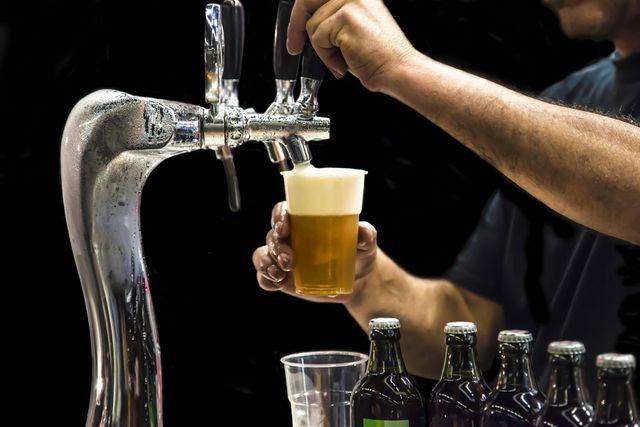 Un uomo mentre versa la birra alla spina in un bicchiere di plastica
