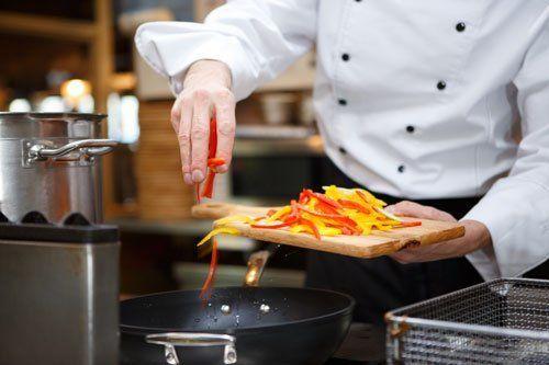 Un cuoco con un camice bianco e nero in cucina mentre aggiunge dei peperoni gialli e rossi tagliati nella padella