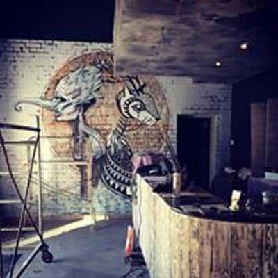 interno di un locale in fase di ristrutturazione con sulla destra un bancone e al muro due strani dipinti