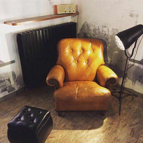 Una stanza con una poltrona di pelle di color senape con un puffo nero davanti, una lampada accesa e dietro dei caloriferi di color nero