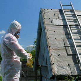 An asbestos consultant working on a roof