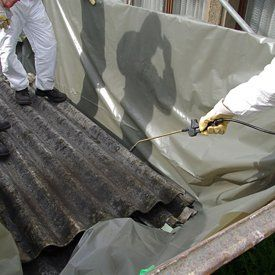 Asbestos experts working on a roof that needs removing