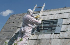 A specialist removing asbestos from a roof