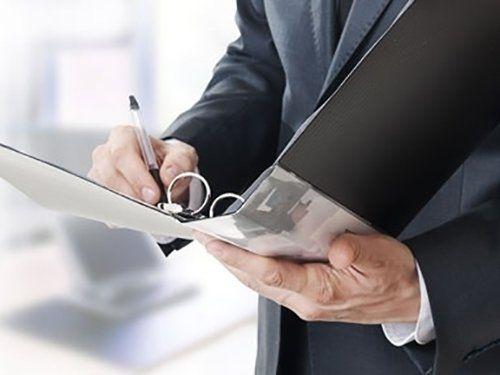 uomo vestito in abito formale firma un documento