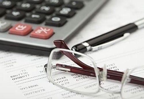 Calcolatrice, penna, occhiali da lettura appoggiati su un foglio di calcolo