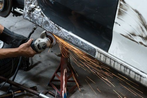 meccanico durante riparazione carrozzeria di un auto