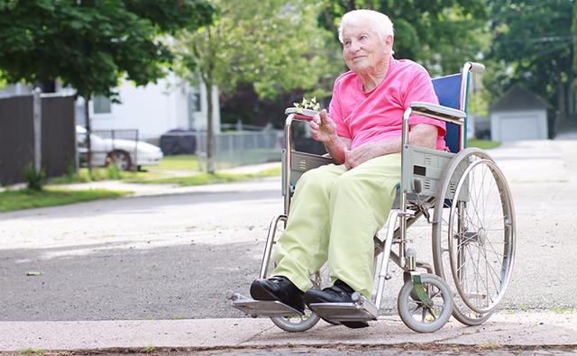 una signora con capelli corti bianchi una maglietta rosa e dei pantaloni verde pisello su una sedia a rotelle