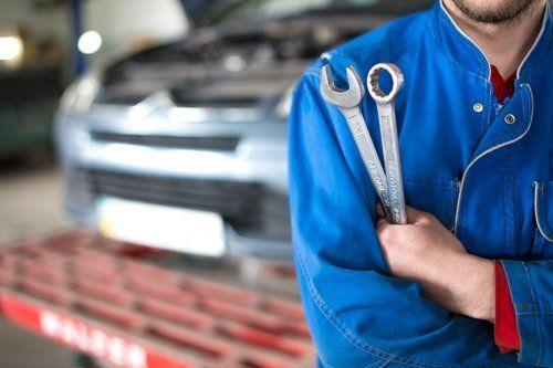 meccanico con strumenti e chiave inglese in officina