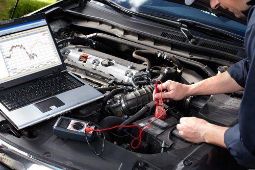 Meccanico che ripara la batteria di un'auto