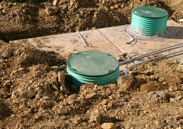 septic tanks being installed into hole in the ground