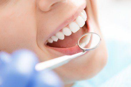 Specialista rivedendo con lo specchio la bocca di un paziente