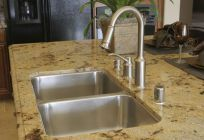 steel kitchen sink on tan granite top