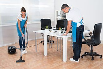 Two workers cleaning an office space