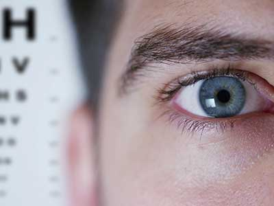 Primo piano di un occhio e un cartello per il test della vista