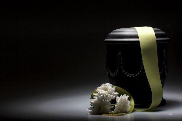 Urna nera con ornamento dorato, un nastro verde e fiori
