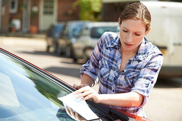 Female motorist looking at parking ticket