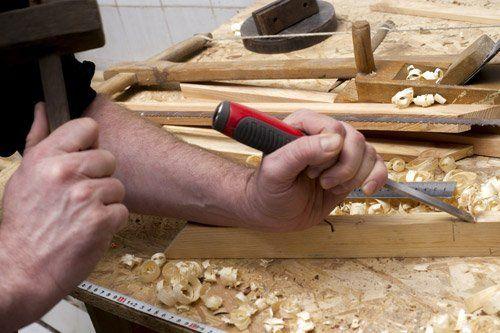 falegname lavora il legno con lo scalpello Morbegno