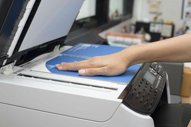 Una mano che poggia un libro su una fotocopiatrice
