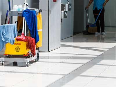 un carrello delle pulizie e un inserviente a lavoro
