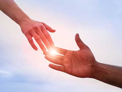 due mani che si sfiorano in controluce