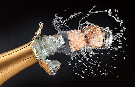 Tre bicchieri di spumante sul vassoio, bottiglia di spumante nel secchiello di ghiaccio