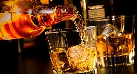 Barman sta versando il whiskey in un bicchiere
