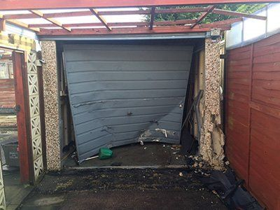 Heavily damaged up and over garage door and concrete posts