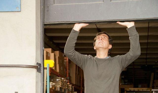 A man raising a manual sectional garage door