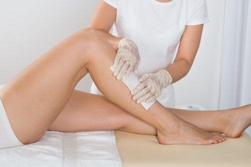 un estetista che applica una striscia epilatoria sulla gamba di una donna