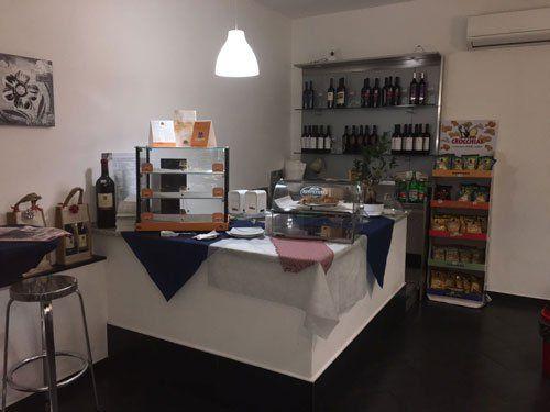 interno del bar con vista del bancone delle piccole vetrinette con dentro delle brioches e dietro uno scaffale con dei vini