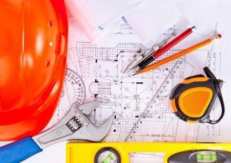 un elmetto,chiave inglese, metro livella, matite e un disegno di un progetto edile