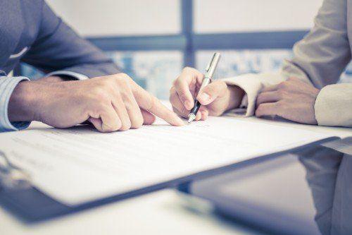 una mano che indica un modulo e un'altra che lo firma
