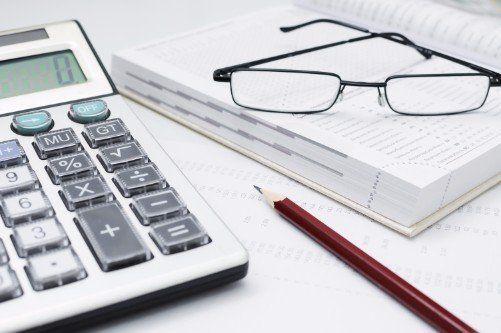 una calcolatrice,una matita e degli occhiali appoggiati su un' agenda