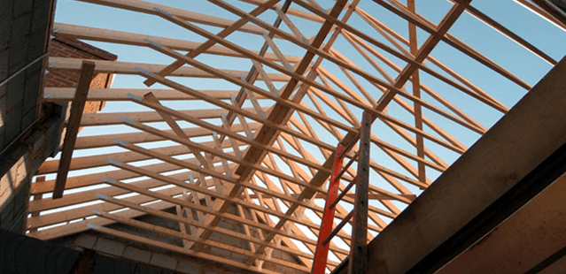 A brand new house being built with the roof trusses being added