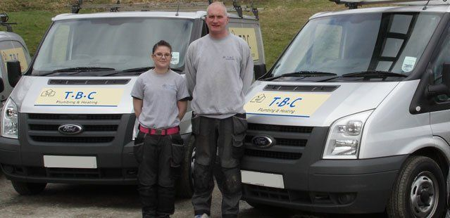 Members of the plumbing and heating team in front of the vans