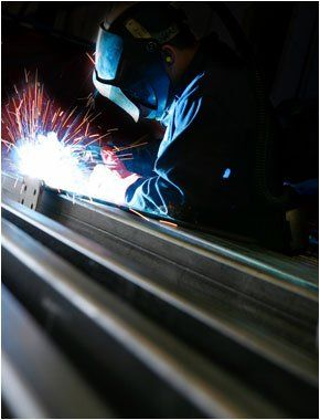 A welder wearing a mask welding some steelwork