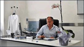 un uomo seduto alla scrivania mentre scrive su un foglio