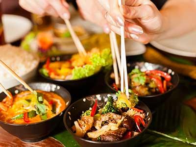 delle mani con delle bacchette e delle ciotole con cibo asiatico