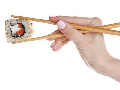 una mano con due bacchette e del sushi