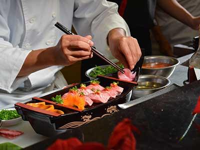 due mani di un cuoco mentre impiatta del sushi