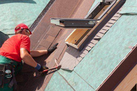 un lavoratore su una piattaforma mentre fa dei lavori sulla facciata d'una casa