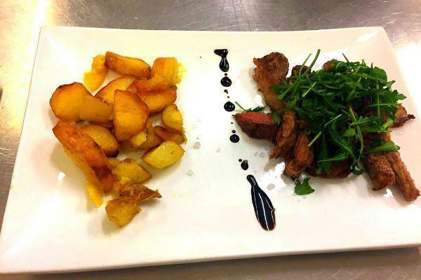 Patate al forno e carne ricoperta di rucola e aceto balsamico